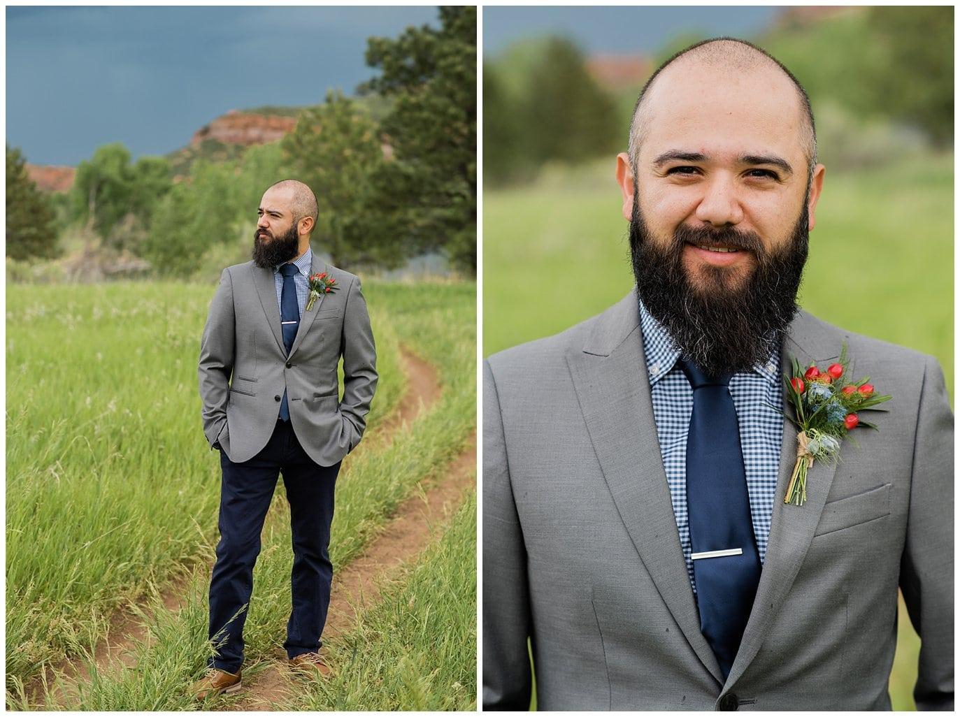 groom in grey suit jacket, navy tie, and black pants photo