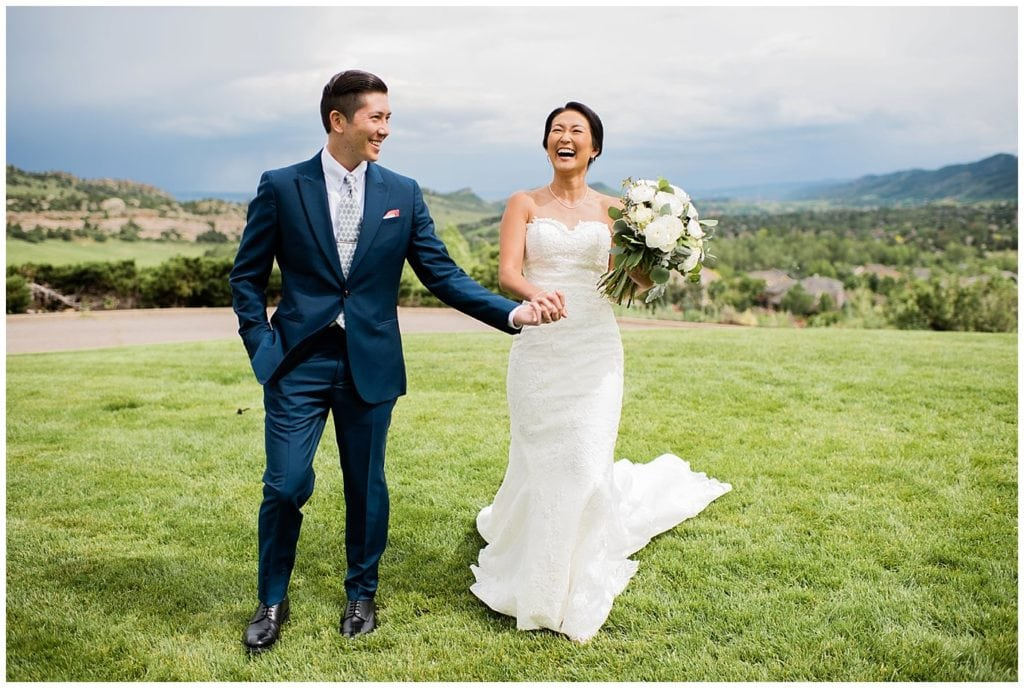 bride and groom walking on front lawn of Manor House wedding by Denver Wedding Photographer Jennie Crate photographer