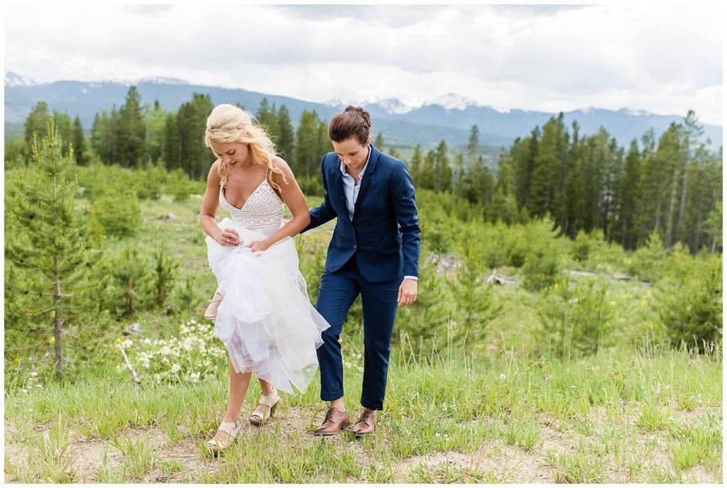 bride and bride walk up hillside on wedding day photo