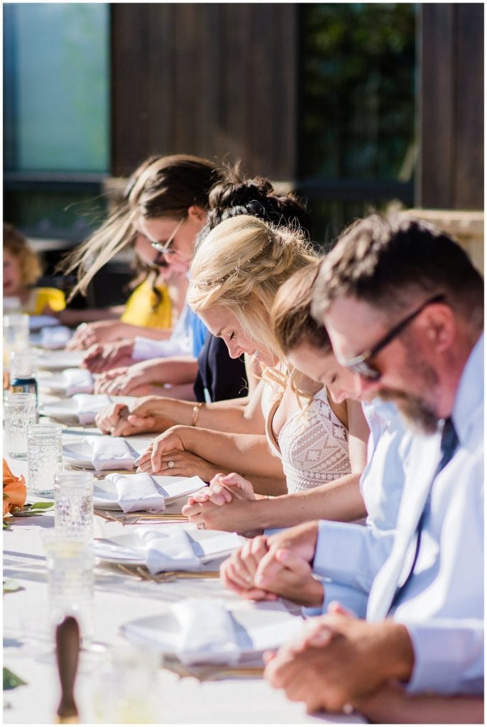 prayer during outdoor microwedding dinner by Colorado Microwedding Photographer Jennie Crate Photographer