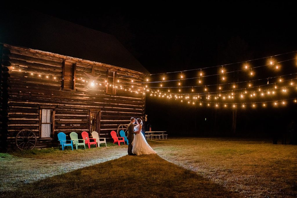 bride and groom night portrait under barn market lights at B Lazy 2 Ranch by Winter Park wedding photographer Jennie Crate