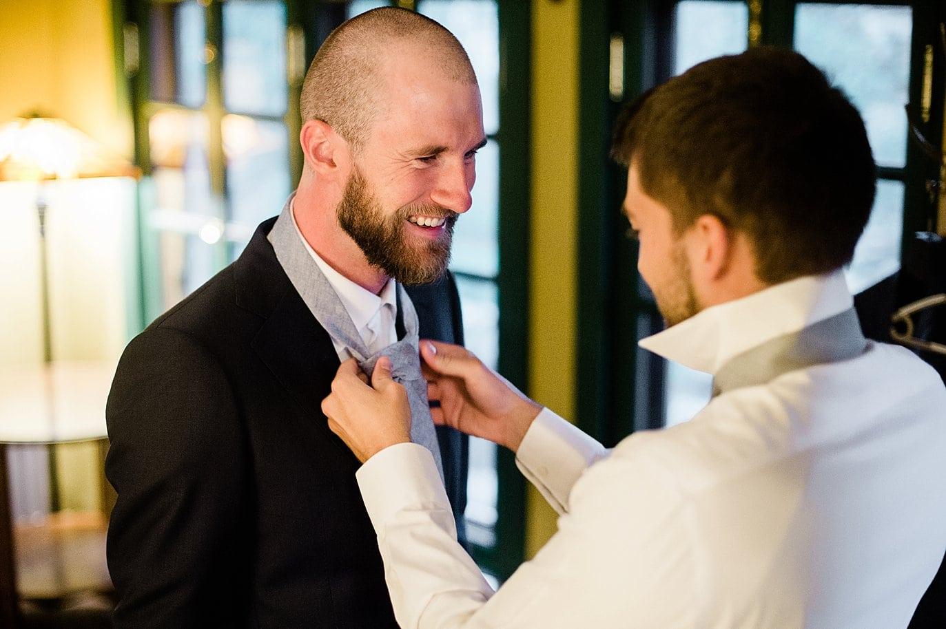 groomsman tying groom tie at golden wedding