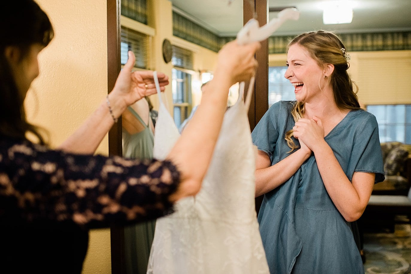 bride excited to put her dress on a colorado outdoor wedding
