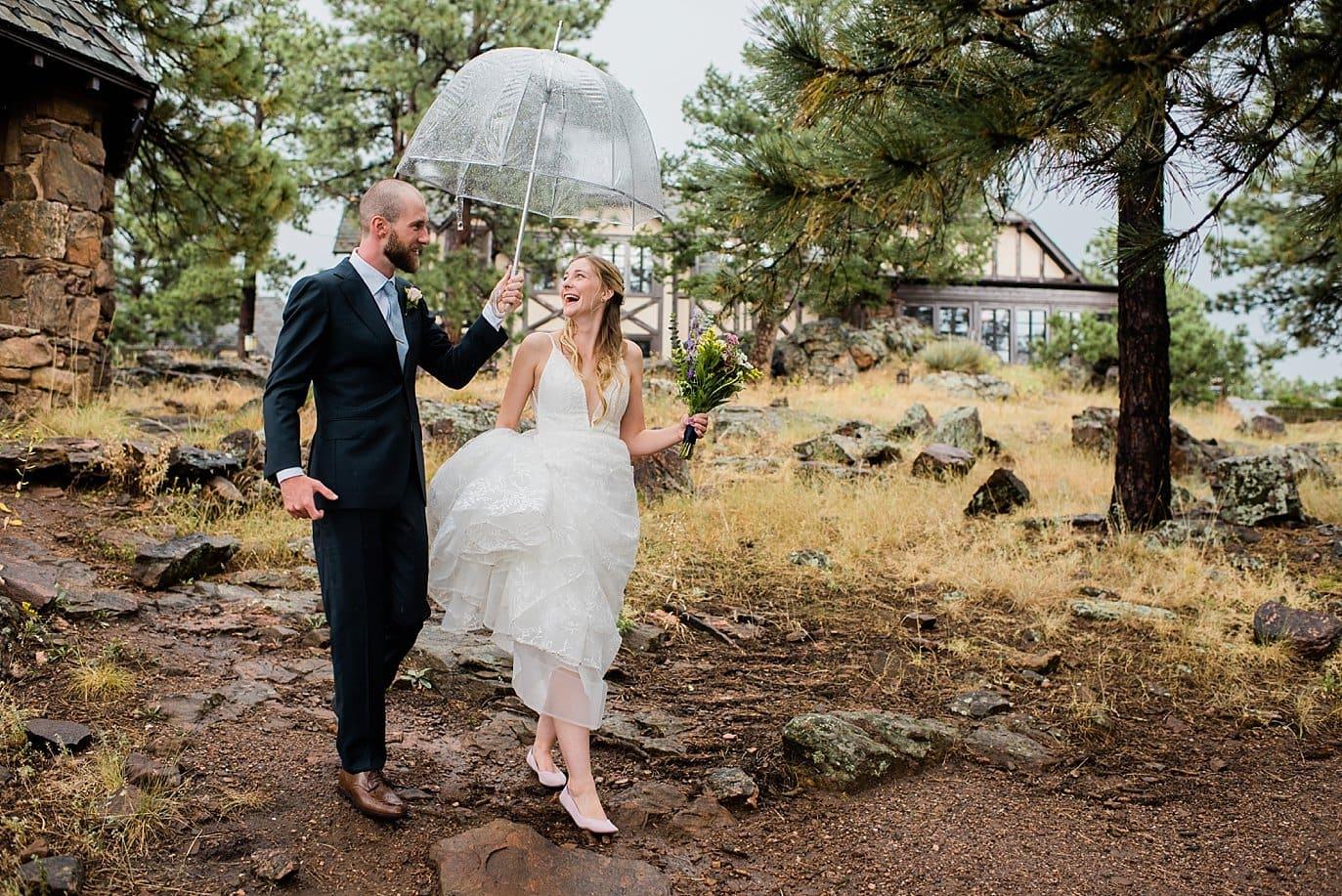 bride and groom with umbrella at rainy Boettcher Mansion wedding