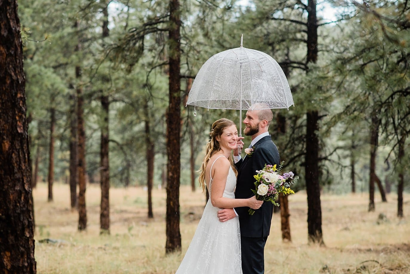 rainy bride and groom in evergreen trees