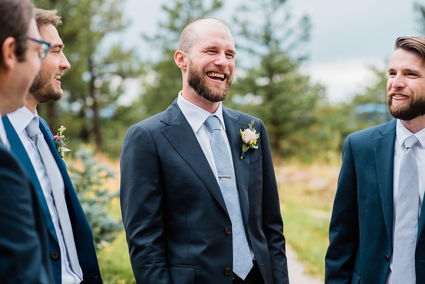 groom laughing with groomsmen at outdoor colorado wedding