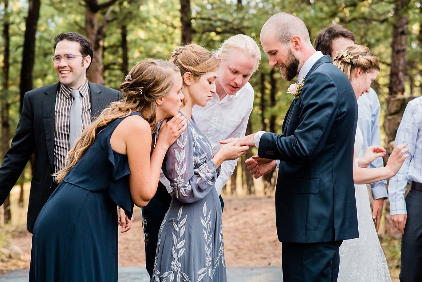 bridesmaids look at grooms wedding ring at Golden wedding