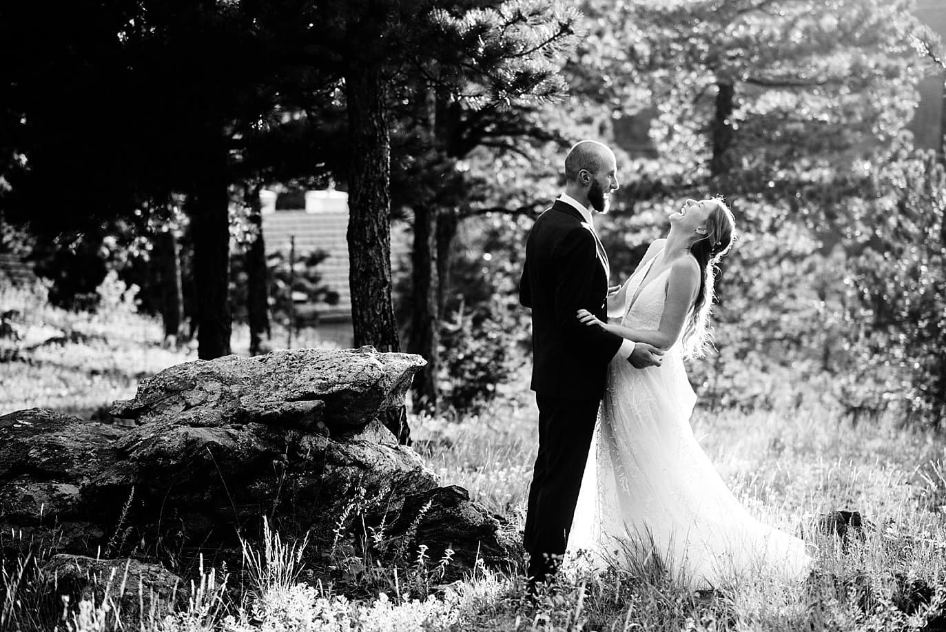 black and white photo of bride laughing in the trees at sunset colorado wedding