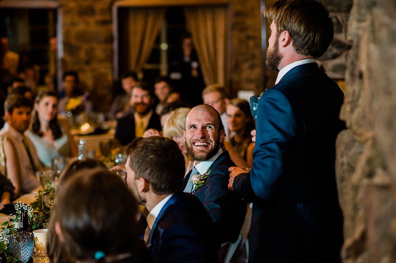 groom laughing during best man speech wedding reception