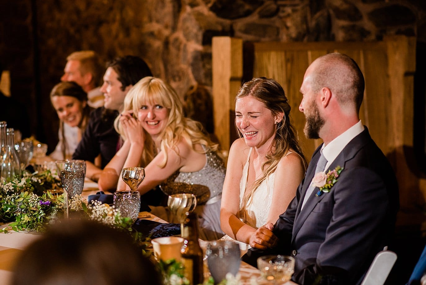 bride laughing during speeches at colorado wedding