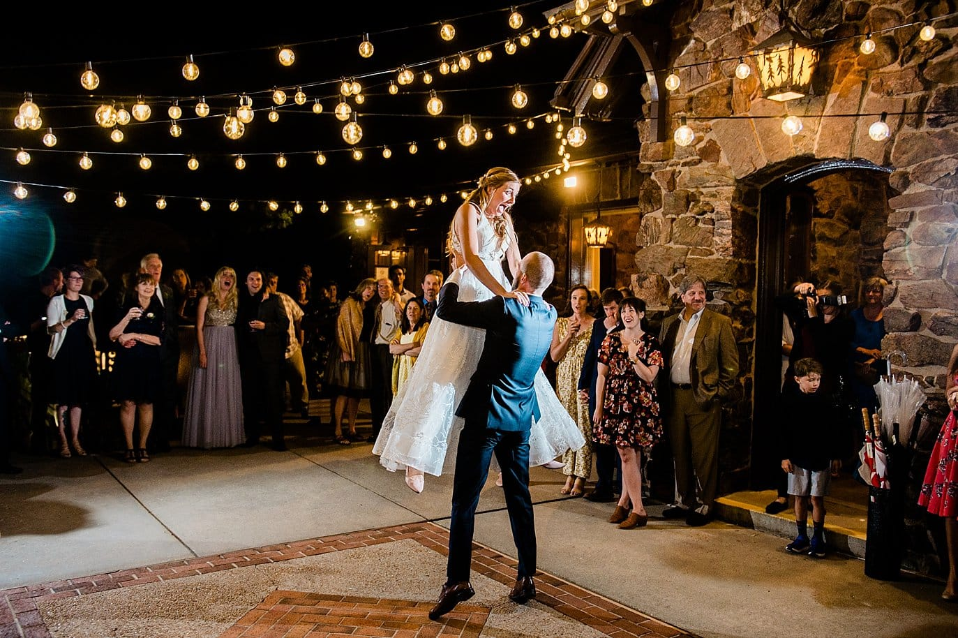 groom lifts bride during first dance on outdoor patio under the market lights