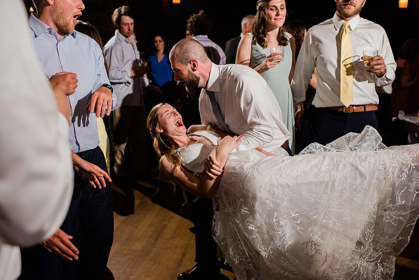 groom dips bride on dance floor at fall colorado wedding