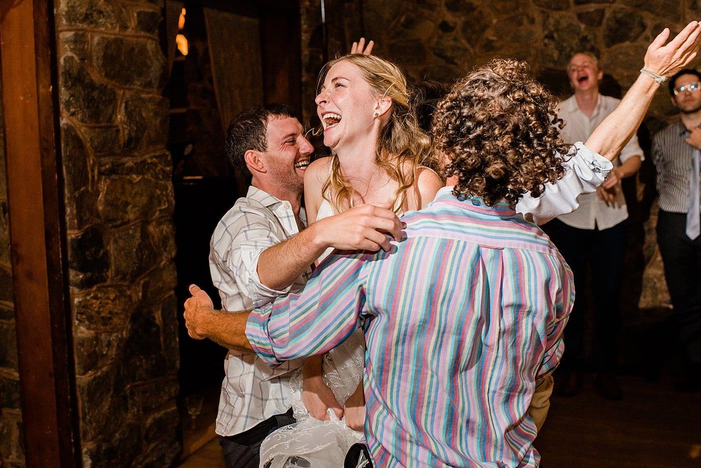 bride group hug on dance floor of intimate wedding