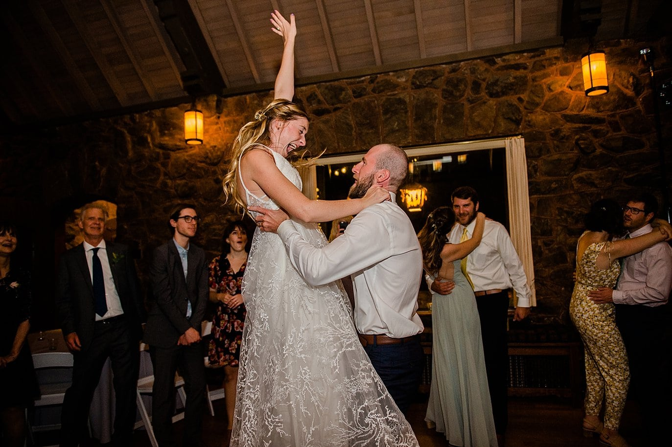 groom lifts bride on dance floor during reception at Colorado wedding