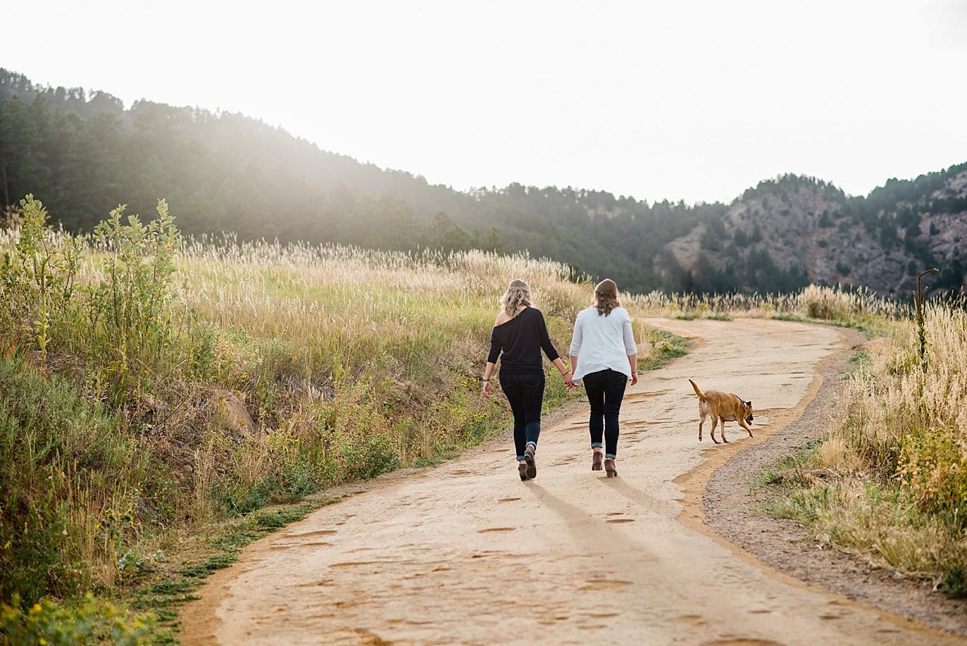 lesbian couple walks with dog at sunset Chautaqua Park engagement by Boulder engagement photographer Jennie Crate