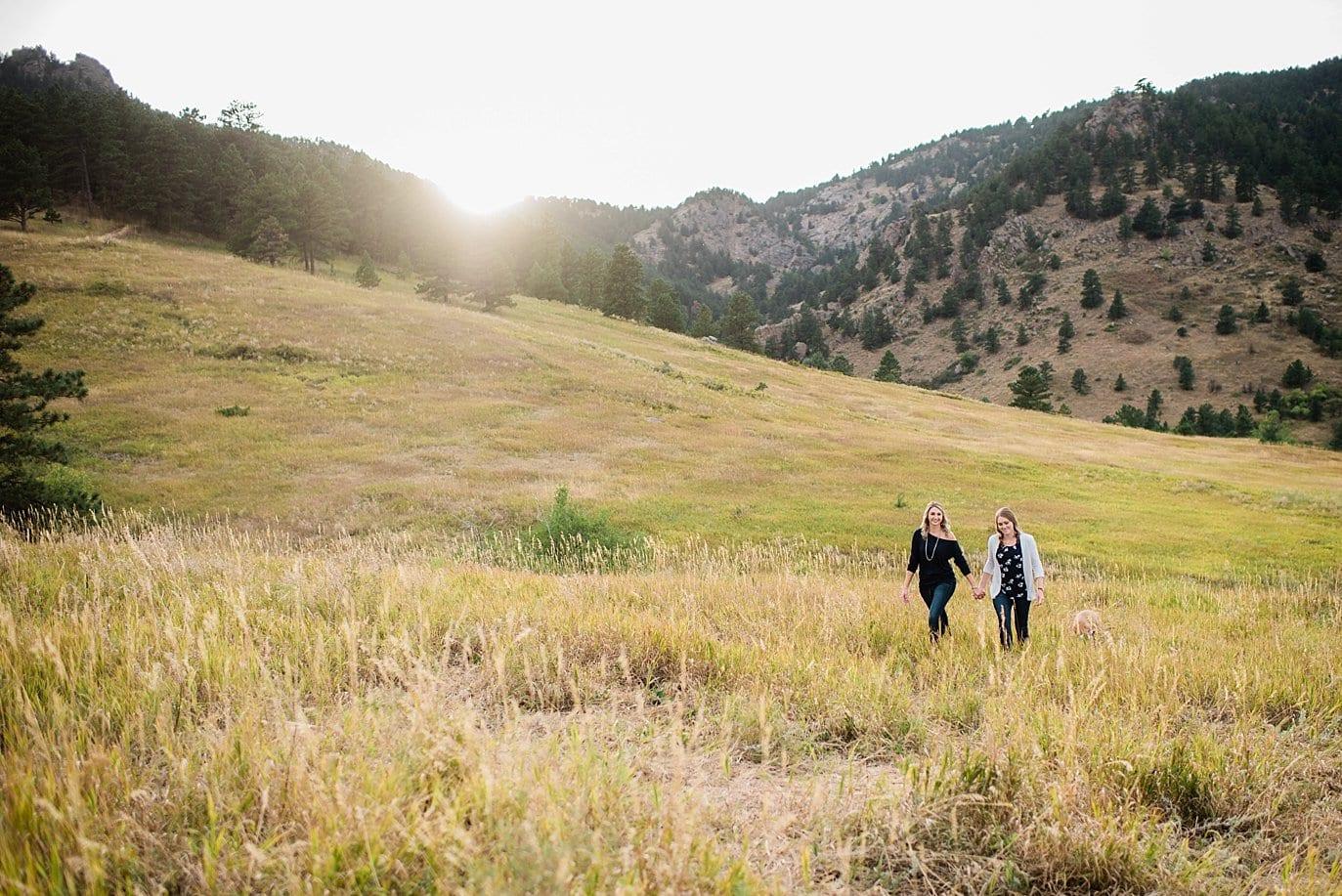 lesbian couple walks through field Chautaqua Park engagement by Boulder engagement photographer Jennie Crate