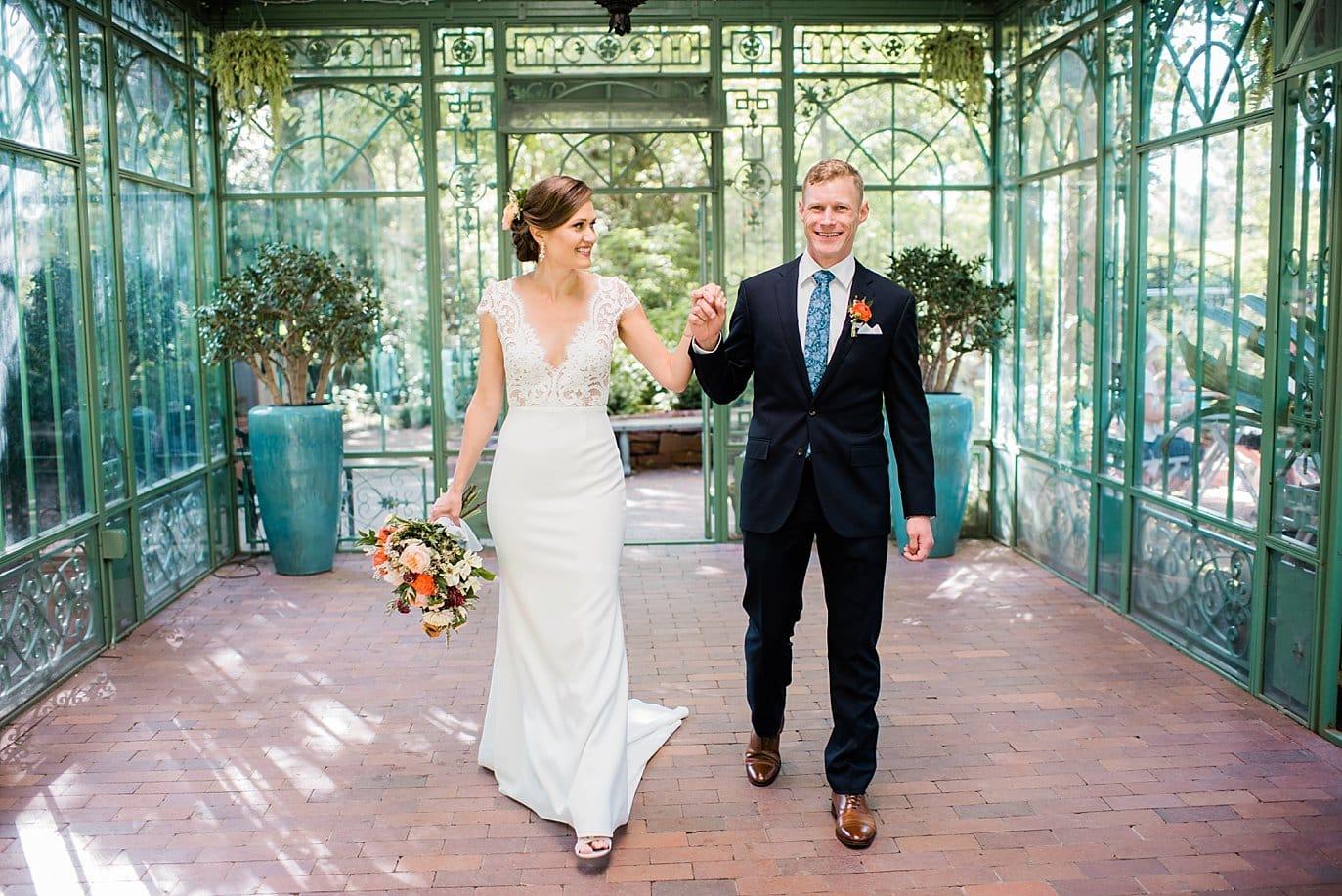 Bride and groom walk in woodland mosaic gardens solarium at Denver Botanic Gardens Wedding by Denver Wedding Photographer Jennie Crate