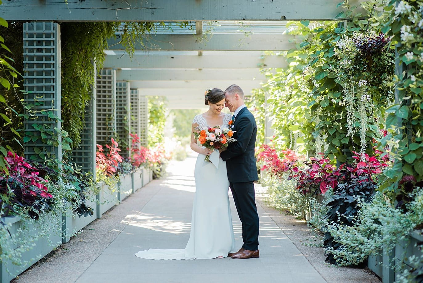 bride and groom under arbor at Denver Botanic Gardens wedding by Denver Wedding Photographer Jennie Crate Photographer