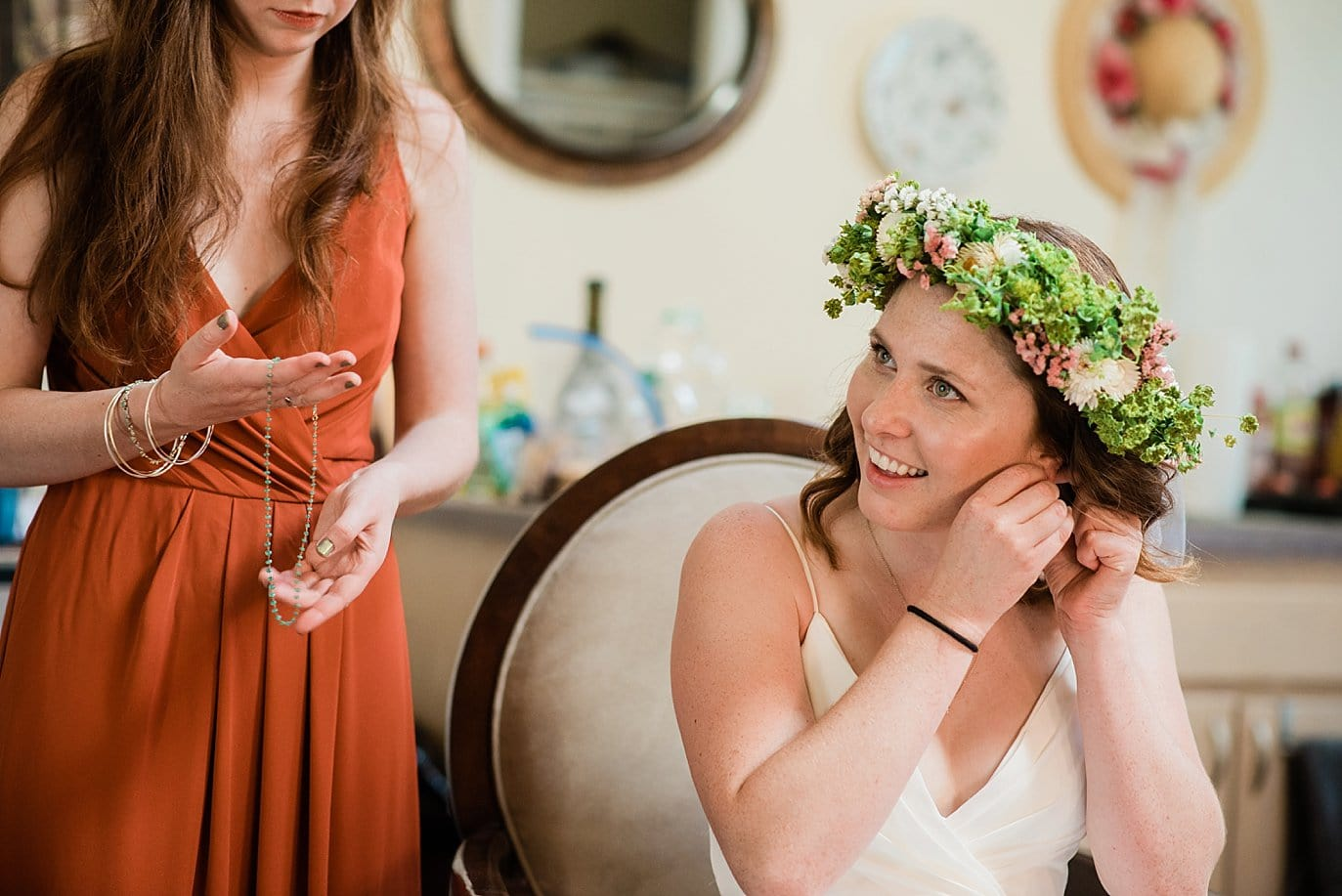 bride in flower crown putting on jewelry on colorado wedding day photo