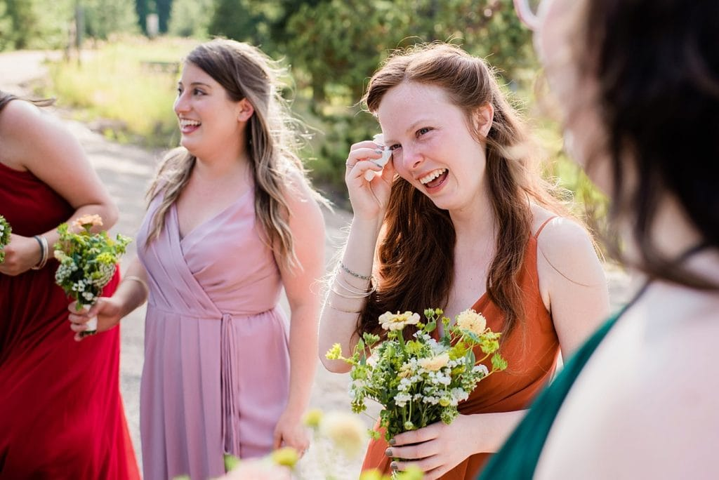 bride's sister crying after wedding ceremony at Evergreen Red Barn wedding by Evergreen wedding photographer Jennie Crate