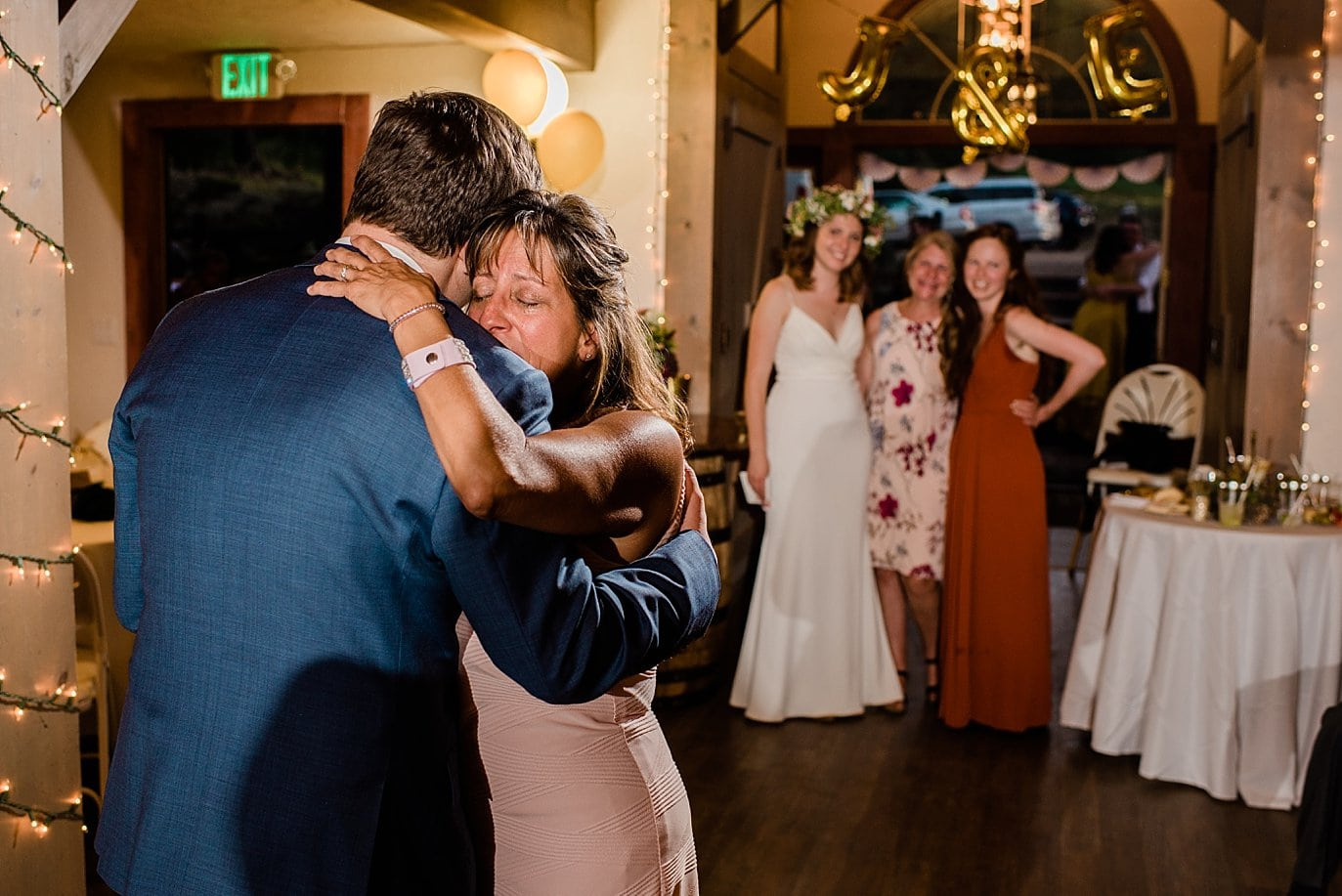 mother and son dance with bride looking on photo