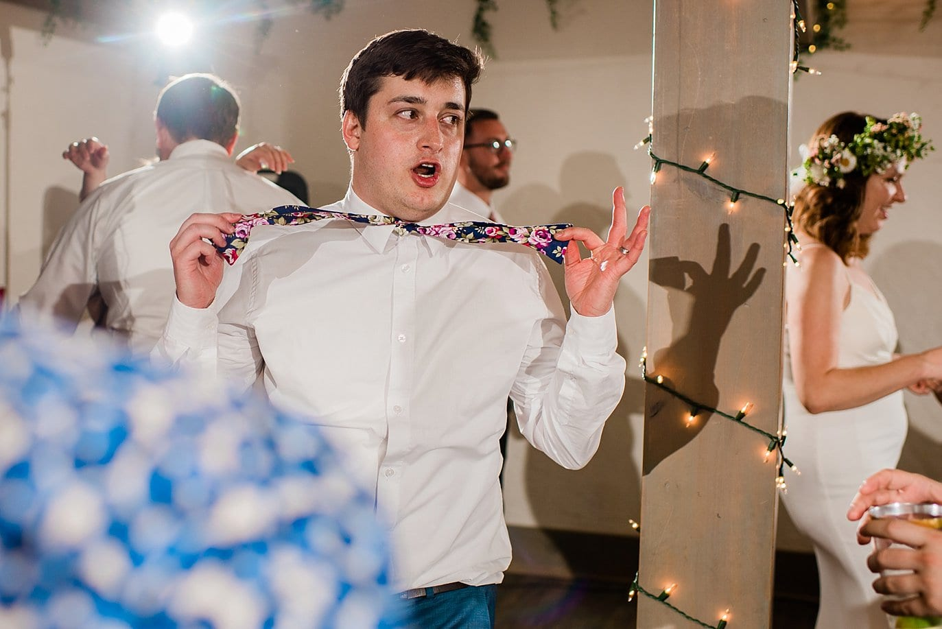 groom dancing with bow tie at wedding reception photo