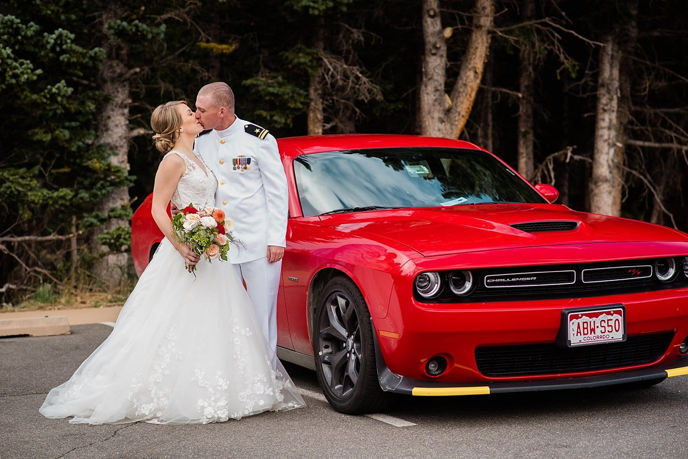 bride and groom by red sports car Colorado elopement
