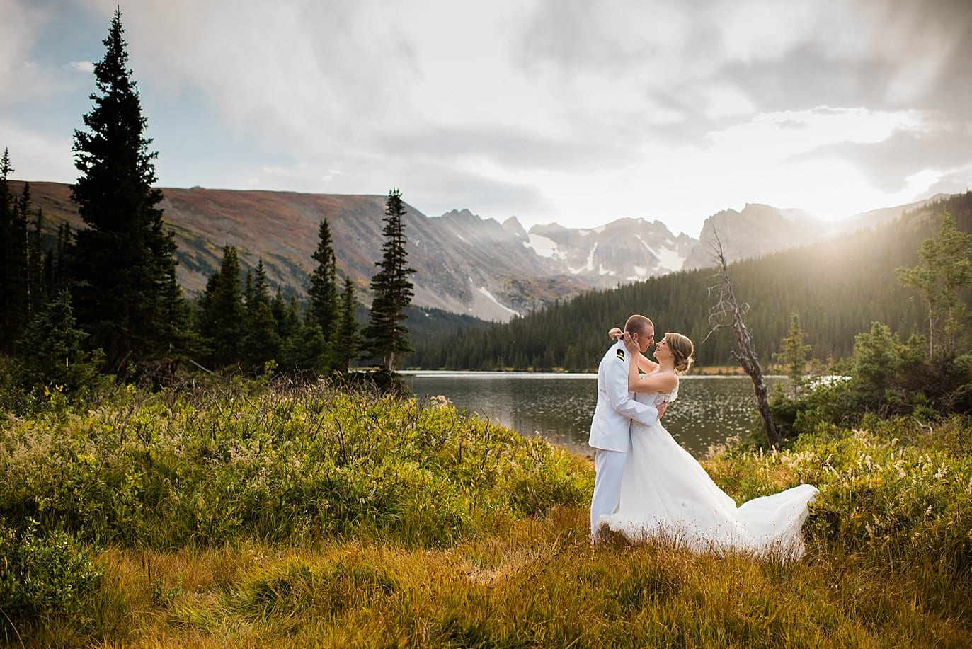 bride and groom in field by Long Lake after Colorado elopement