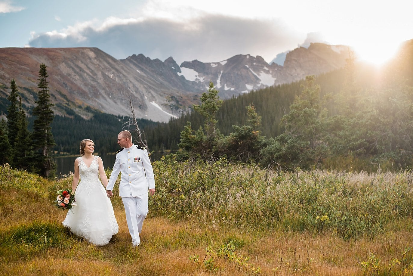 bride and groom walk in field with view of colorado mountains