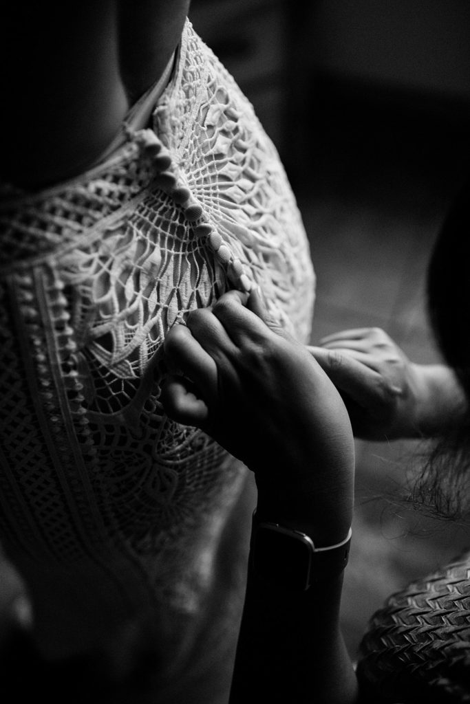 bride getting dress laced up photo