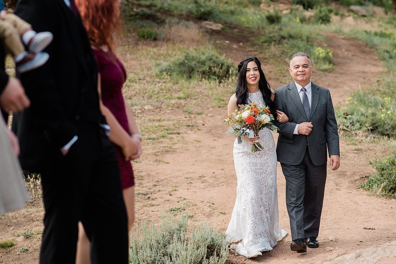Bride walking down aisle as guests sing at Rocky Mountain National Park Wedding by RMNP Wedding Photographer Jennie Crate