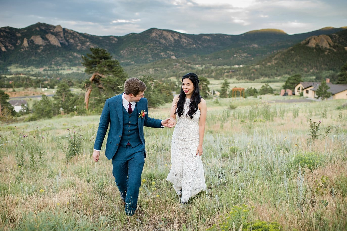 Bride and groom walking by lodge at Rocky Mountain National Park Wedding by Denver Wedding Photographer Jennie Crate