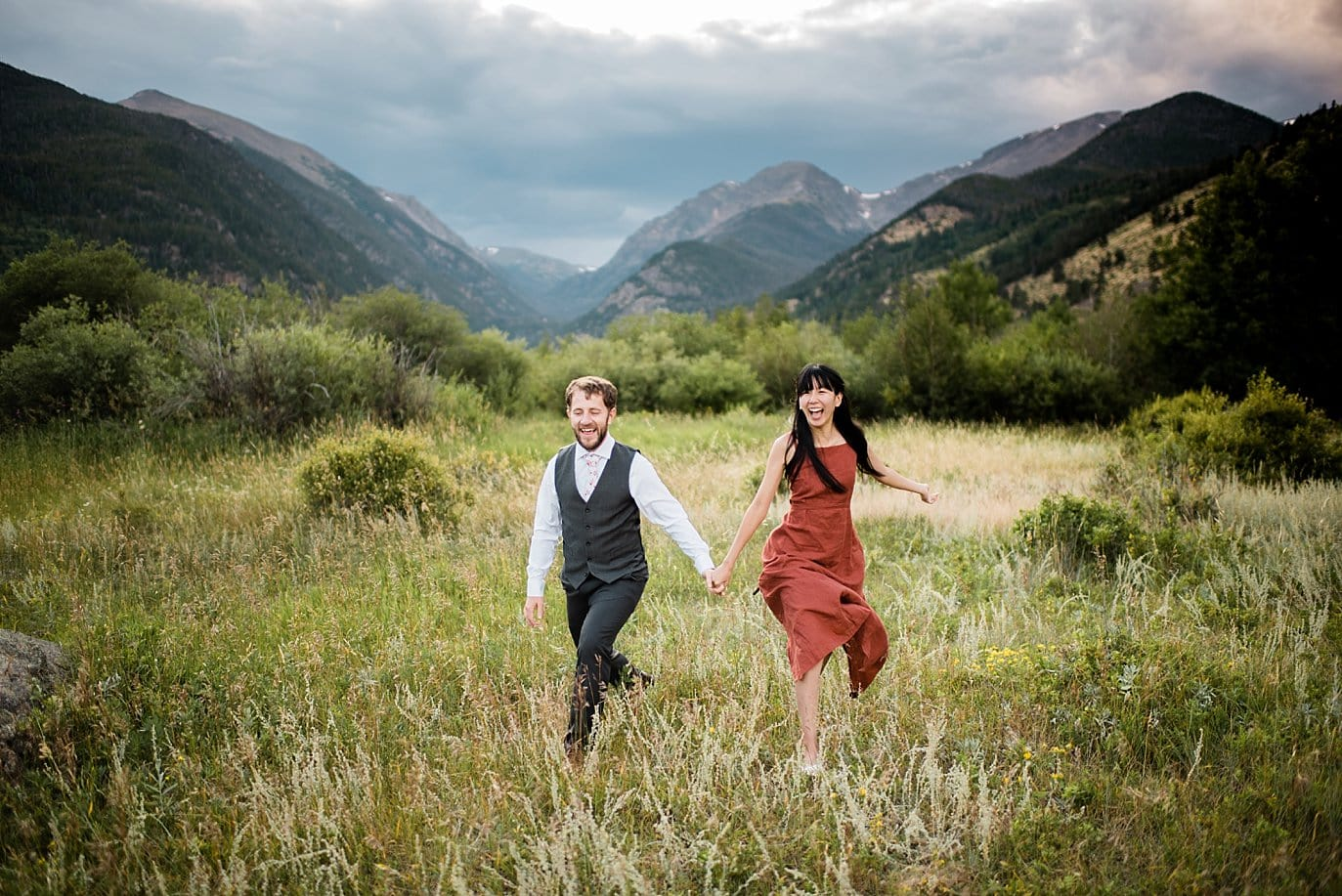 engaged couple running through the National Park in Colorado at Lawn Lake Trailhead Engagement