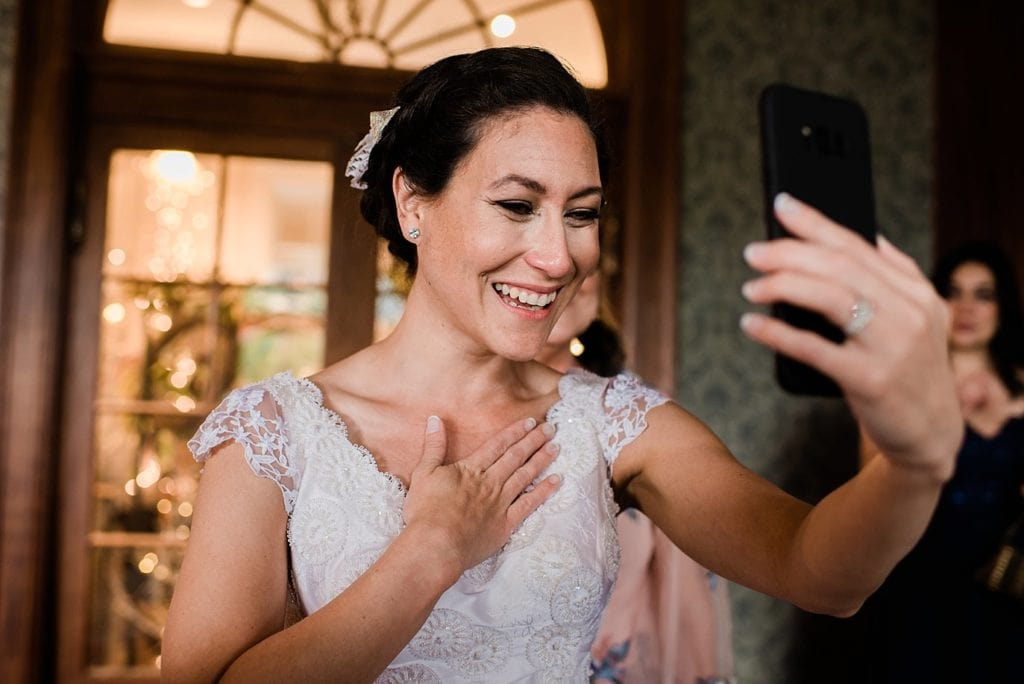 bride doing FaceTime call with relatives on wedding day photo