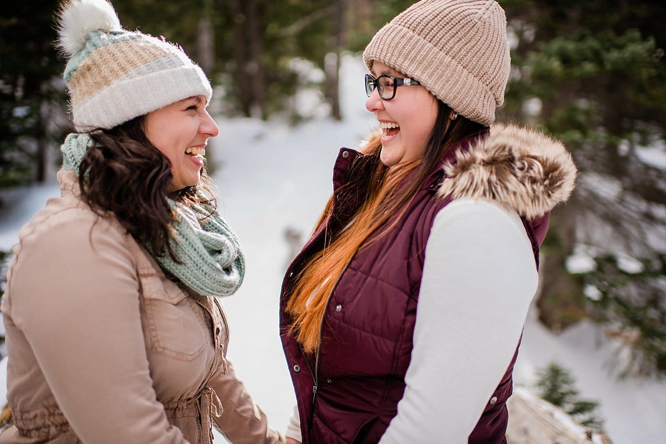 two women laughing during Alberta Falls Rocky Mountain National Park winter hiking engagement by RMNP engagement photographer Jennie Crate, Photographer