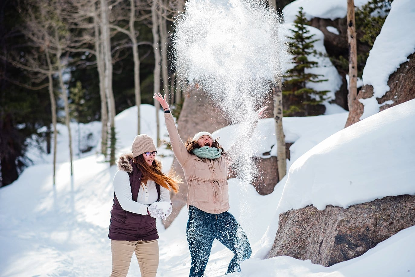 same-sex couple plays in snow Alberta Falls Rocky Mountain National Park winter hiking engagement by Rocky Mountain engagement photographer Jennie Crate, Photographer