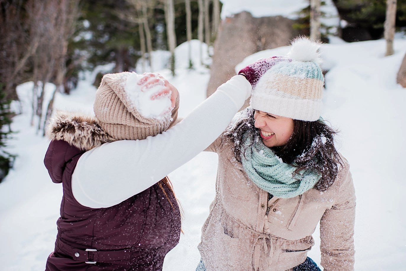 two brides playing in snow at Alberta Falls Rocky Mountain National Park winter hiking engagement session by Denver engagement photographer Jennie Crate, Photographer