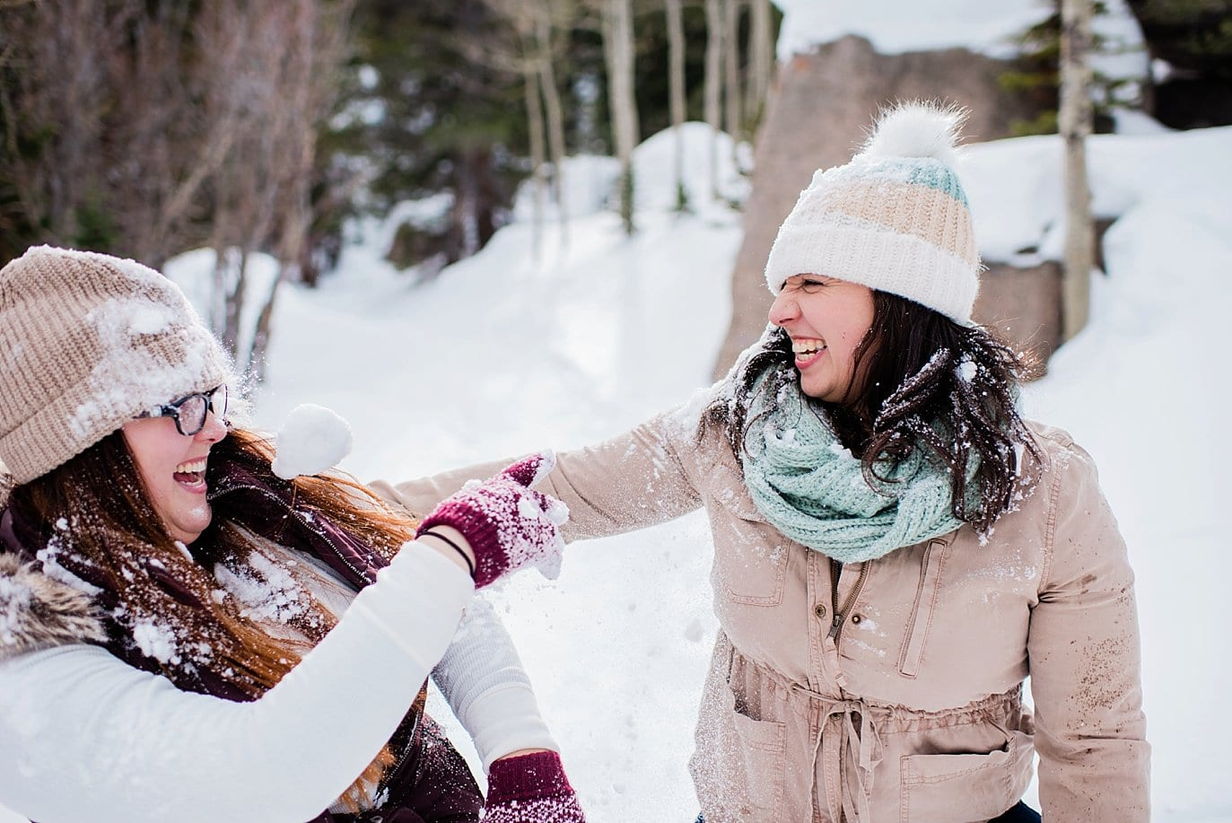 lesbian couple snow fight during Alberta Falls Rocky Mountain National Park winter hiking engagement by Boulder engagement photographer Jennie Crate, Photographer