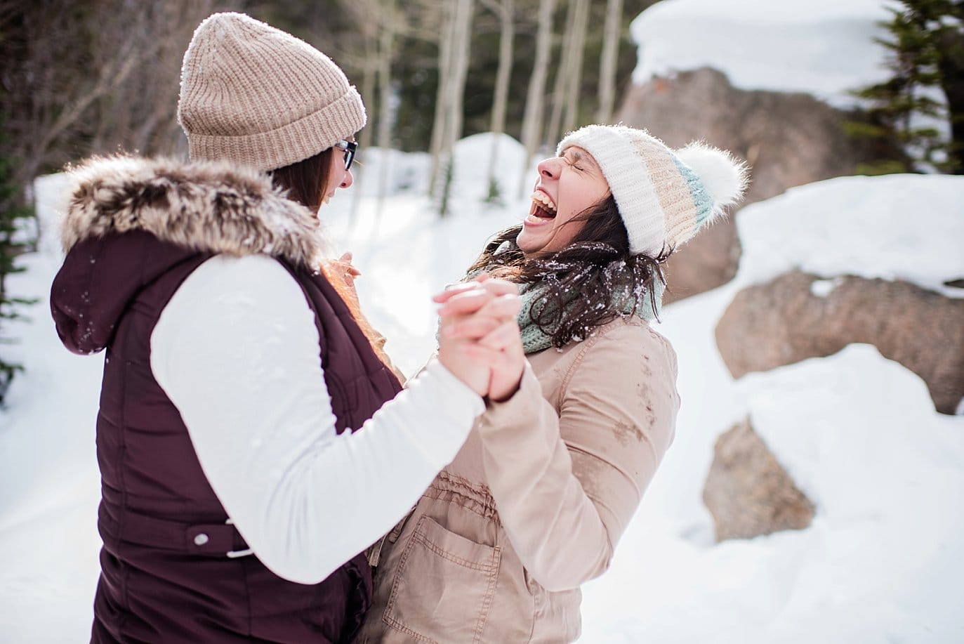 queer couple laughing in snow Alberta Falls Rocky Mountain National Park winter hiking engagement by Denver engagement photographer Jennie Crate, Photographer