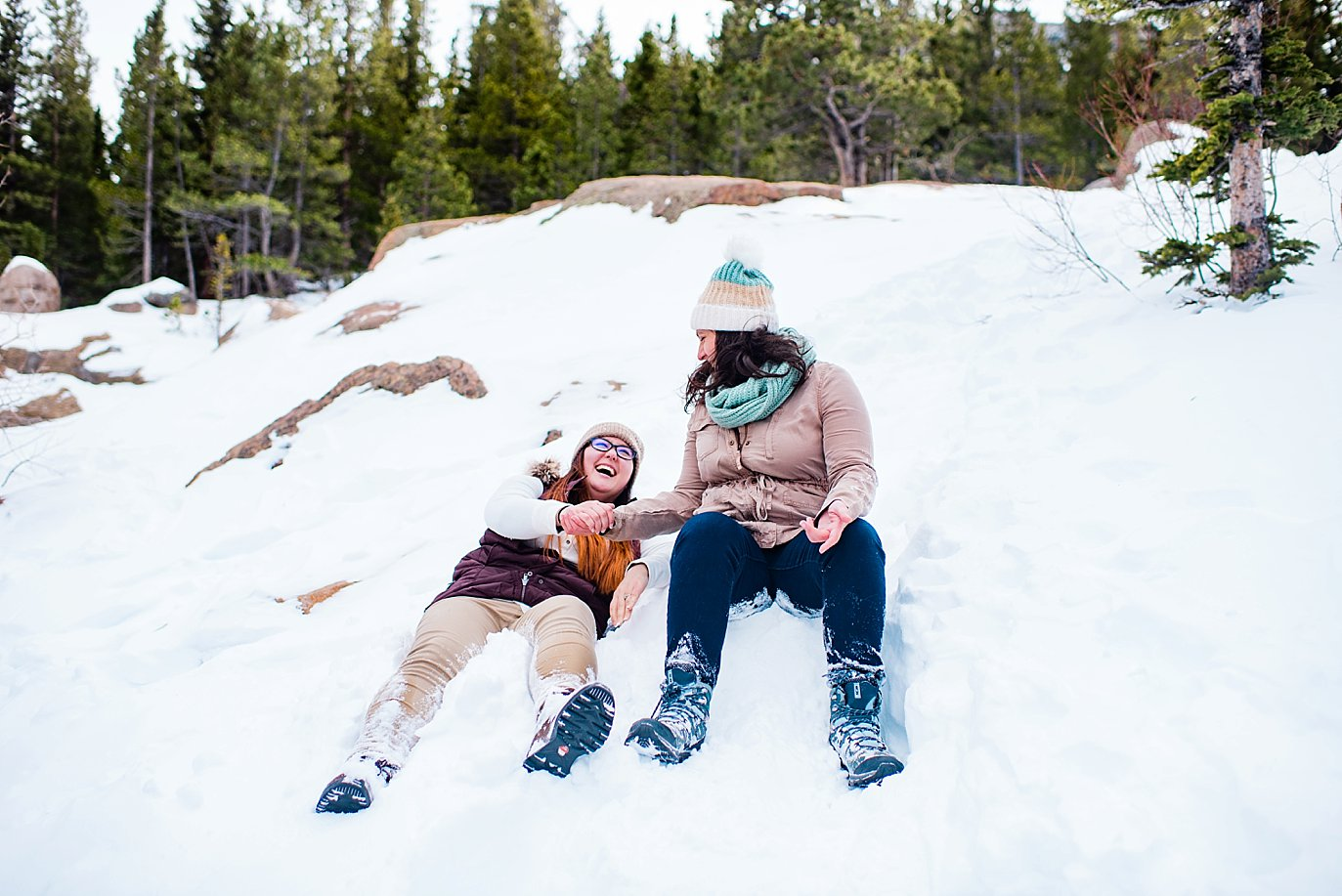 queer couple sliding down snow on butts Alberta Falls Rocky Mountain National Park winter hiking engagement by Boulder engagement photographer Jennie Crate, Photographer