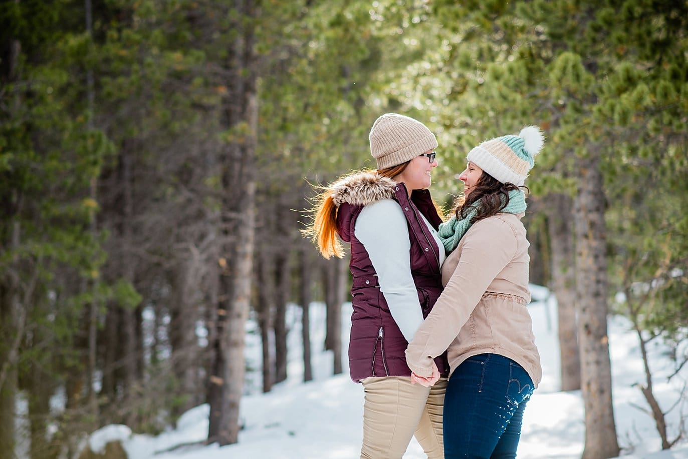 two brides cuddling in snow and sun Alberta Falls Rocky Mountain National Park winter hiking engagement by Denver engagement photographer Jennie Crate, Photographer