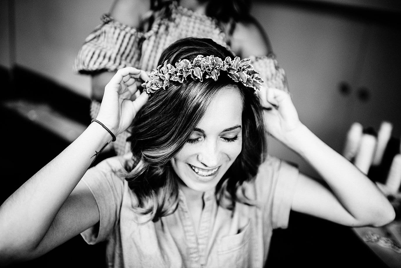 bride puts on floral crown at Arapahoe Basin wedding by Breckenridge wedding photographer Jennie Crate