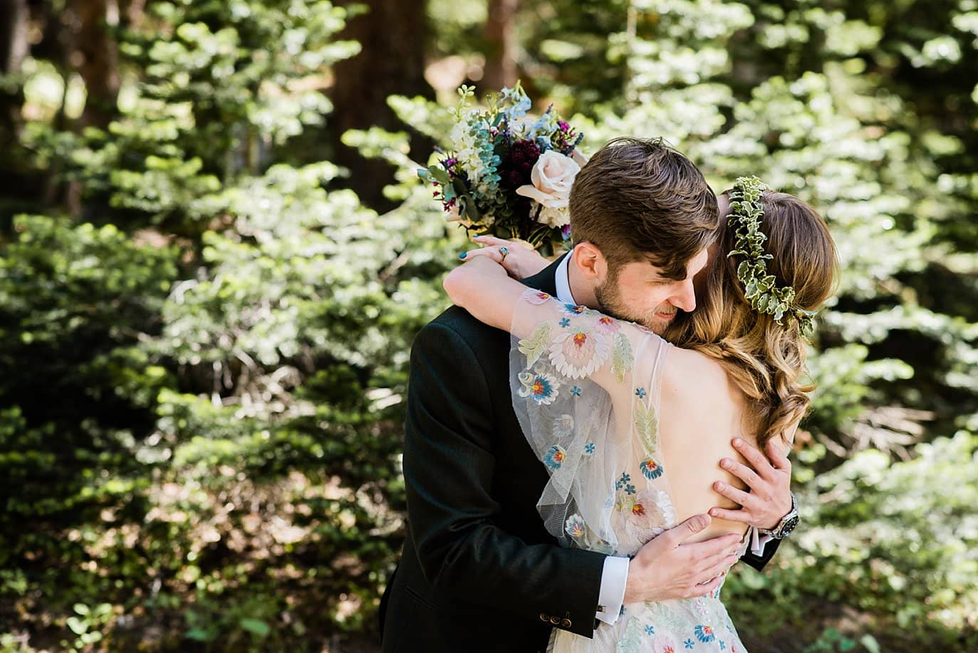 bride and groom embrace after first look in trees at Arapahoe Basin wedding by Breckenridge wedding photographer Jennie Crate