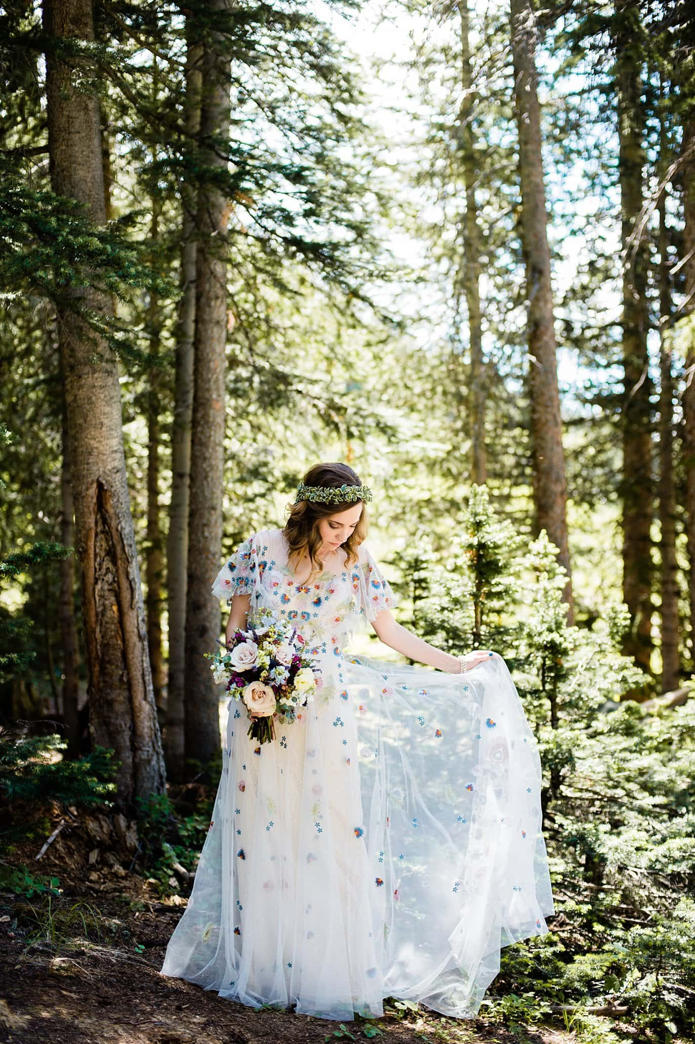 bride in unique floral chiffon wedding dress in sunlight in trees at Arapahoe Basin wedding by Frisco wedding photographer Jennie Crate