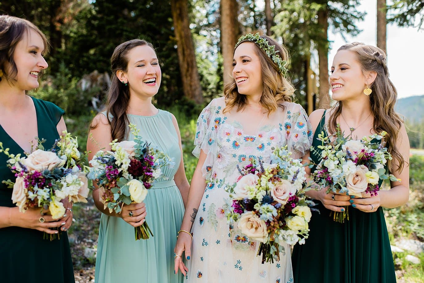 bride in unique boho floral dress and bridesmaids in green dresses at Arapahoe Basin wedding by Rocky Mountain Wedding photographer Jennie Crate photographer