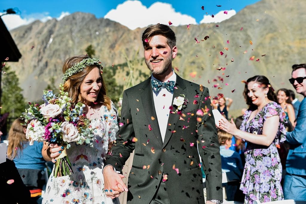 bride and groom leave ceremony in shower of flower petals at Arapahoe Basin wedding by Vail wedding photographer