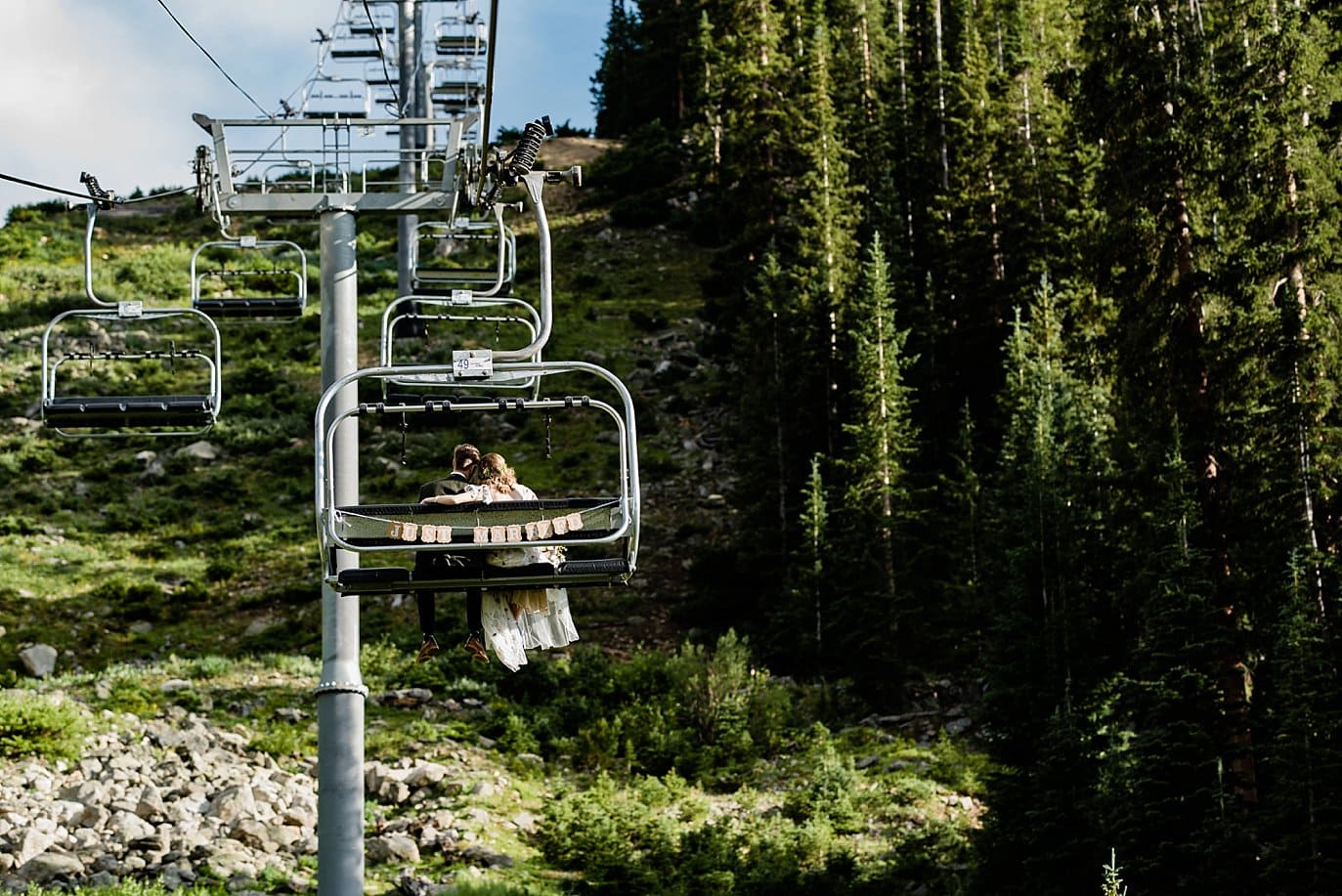 bride and groom ride chair lift after wedding ceremony at Black Mountain Lodge by at Arapahoe Basin wedding by Vail wedding photographer