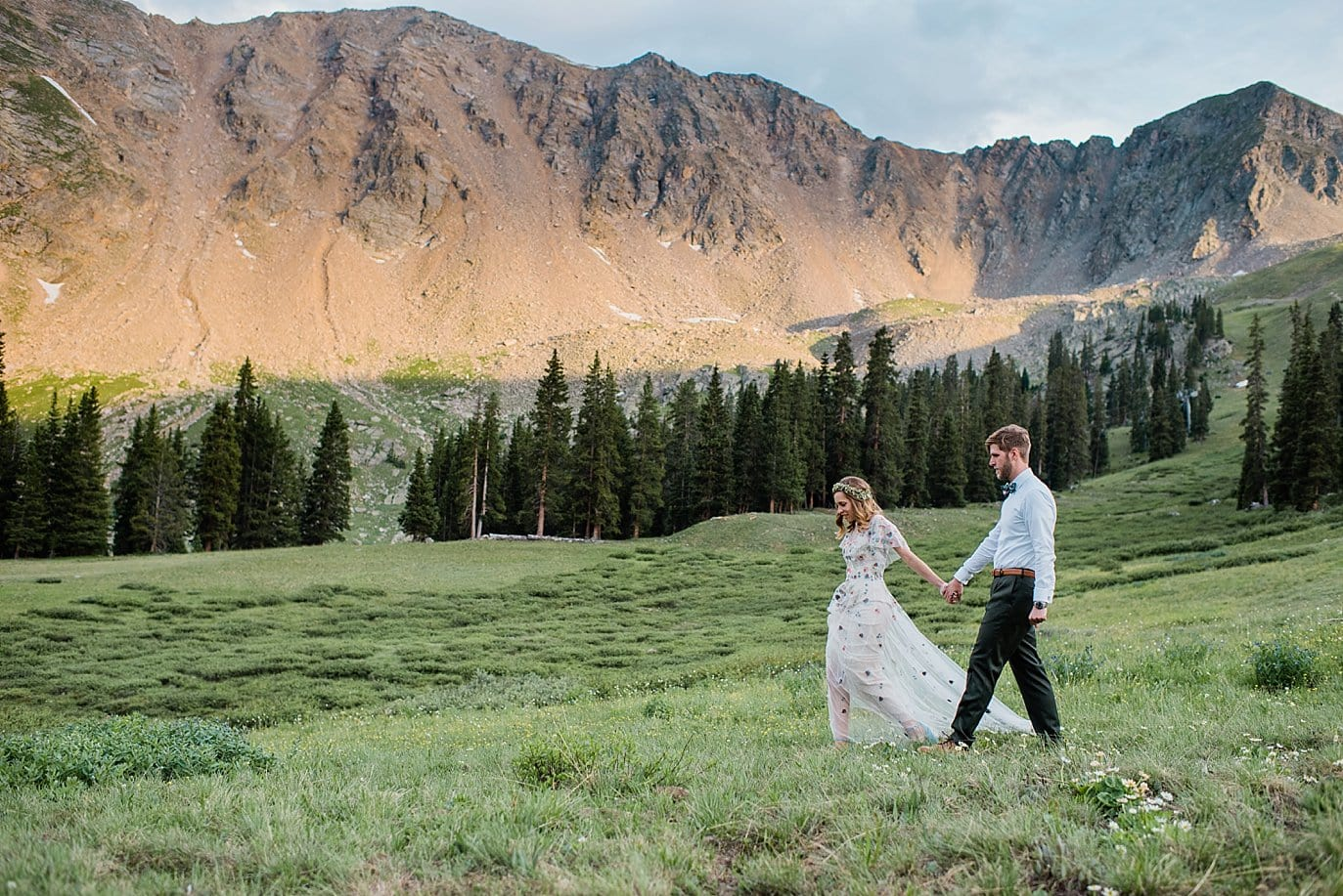bride and groom outdoors at top of Arapahoe Basin at sunset alpenglow at Arapahoe Basin wedding by Vail wedding photographer