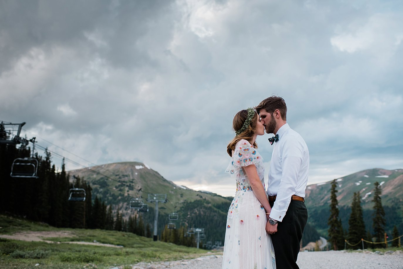 bride and groom sunset portrait at top of black mountain lodge at Arapahoe Basin wedding by Vail wedding photographer