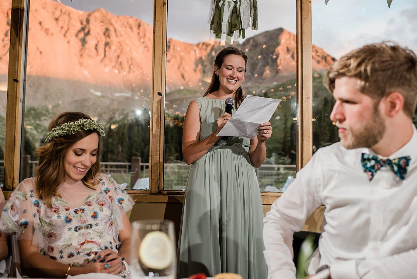 sister of bride reads toast during sunset at Black Mountain lodge wedding by Keystone wedding photographer Jennie Crate Photographer